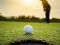 Golf Spieler am Abend beim Sonnenuntergang