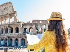 Frau von hinten fotografiert beim schauen auf den Stadtplan an einem heißen Tag, im Hinergrund das Colosseum von Rom