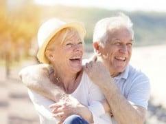 Glückliches Seniorenpaar an einem sonnigen Tag am Strand